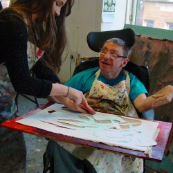 Volunteer helping artist at Project Ability