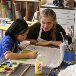 Volunteer Elisa Coffey helps young artist