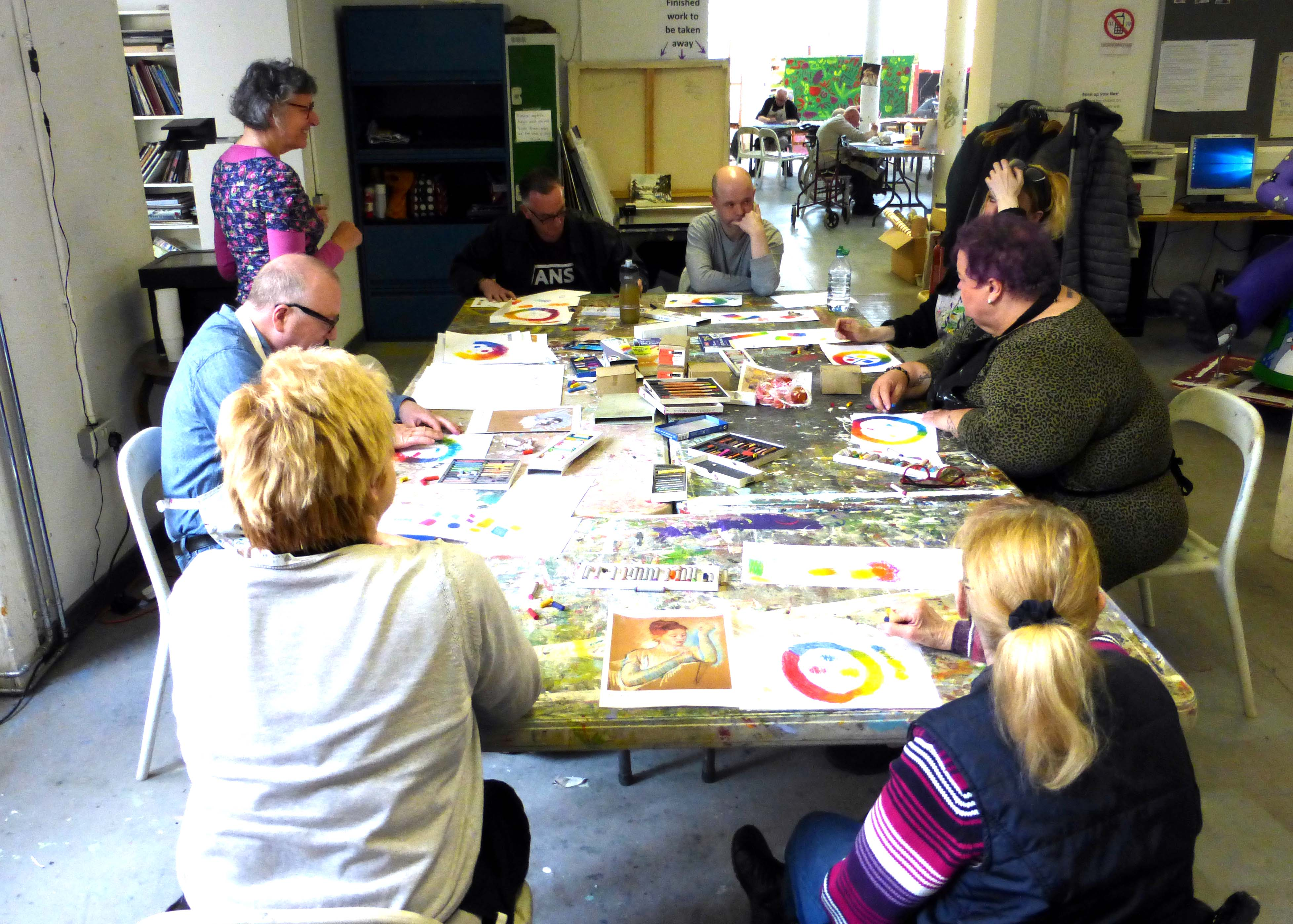 volunteer at table helping artists at Project Ability