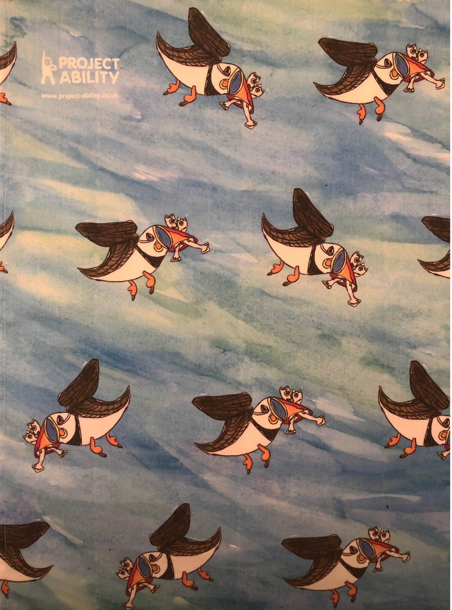tea towel of blue sky with puffins by Cameron Morgan