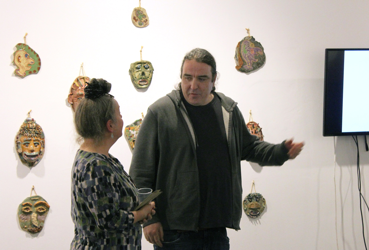 Two of the exhibiting artists standing in the gallery talking
