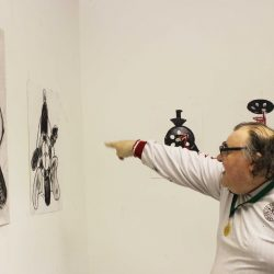 Artist, John Cocozza, pointing at at some collage work pinned to the gallery wall