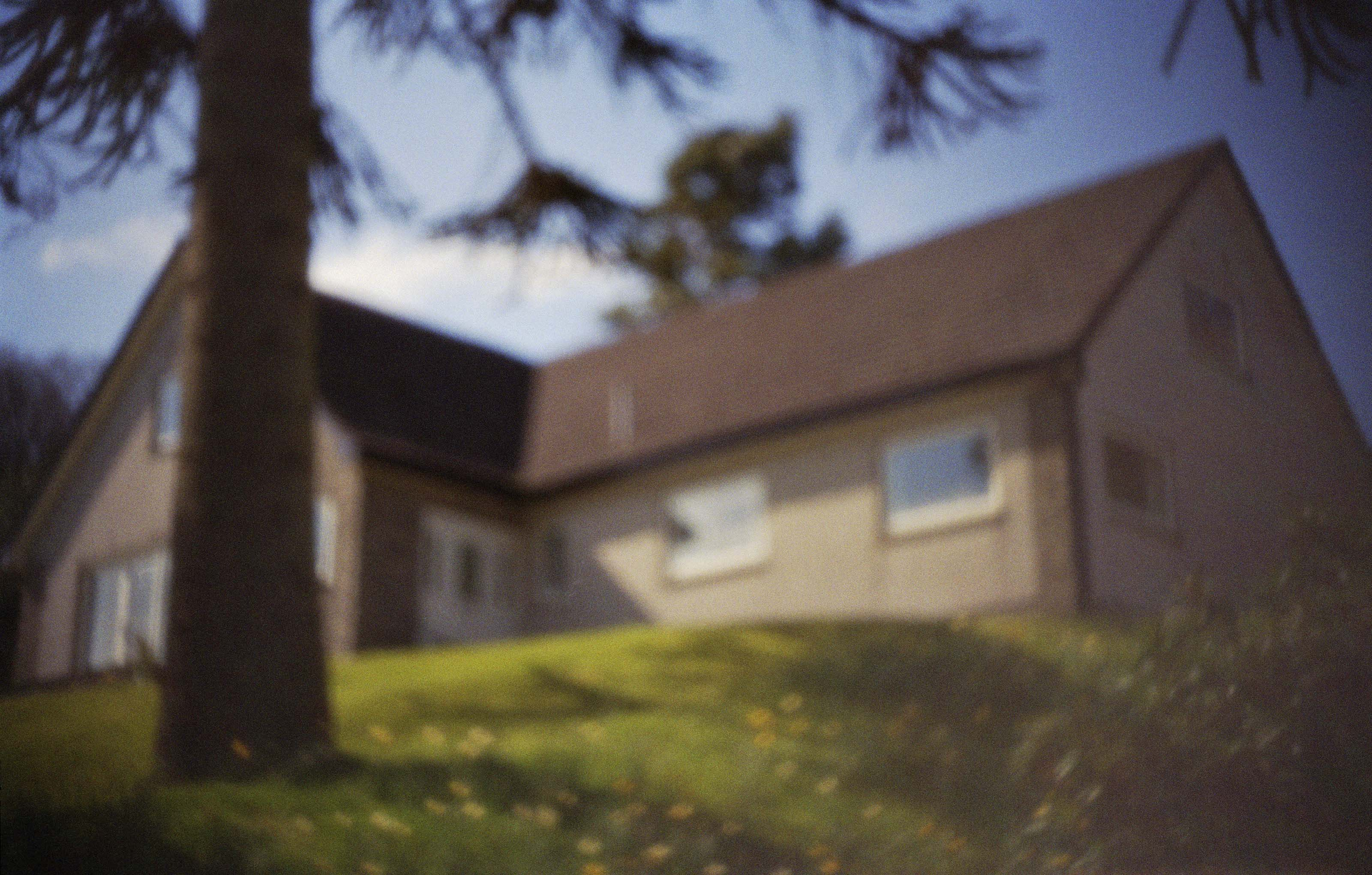 Pinhole photograph of a corner house with a grassy hill and a large tree to the left. Image by Dylan Esposito