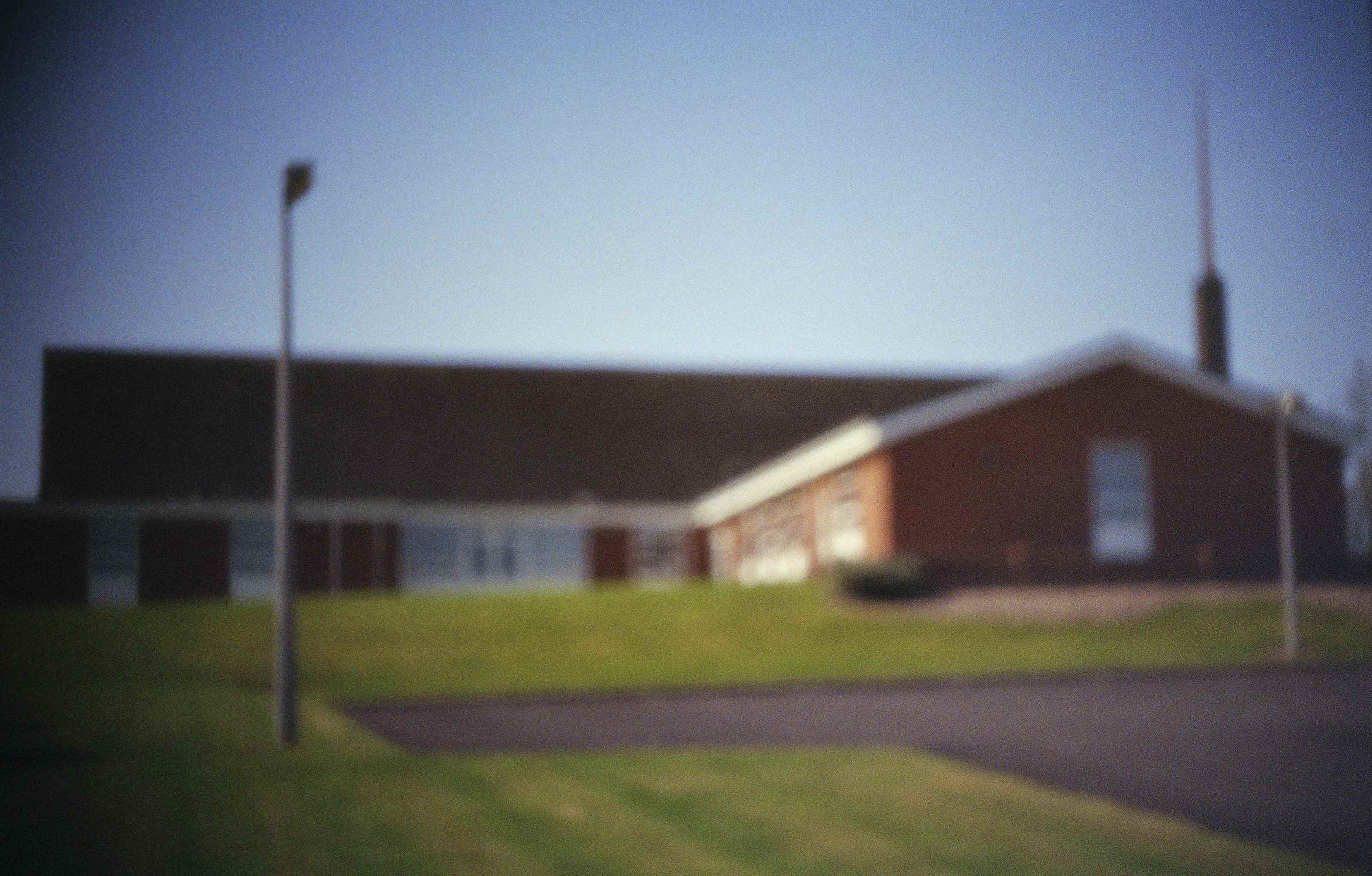 Pinhole photograph of a corner house with grass and a lamp post in the front.. Image by Dylan Esposito