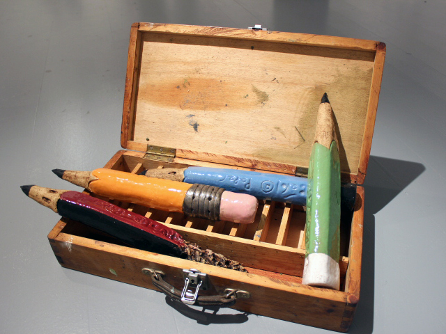 gigantic ceramic pencils in a large wooden box