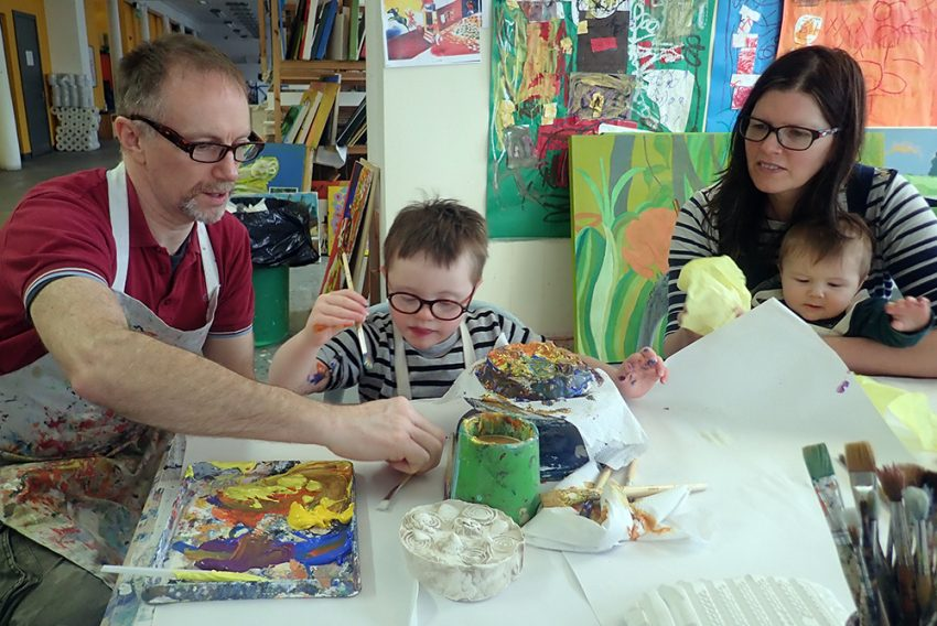 A man and a woman sitting at a table helping a young boy with Down's Syndrome to paint