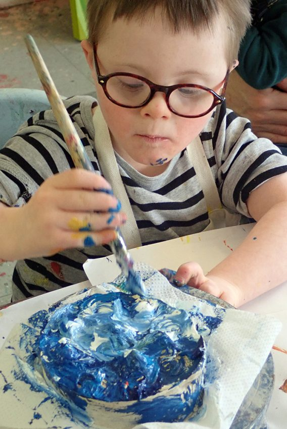 young boy with Down's Syndrome painting with blue and white paint. The boy has blue paint on his chin.