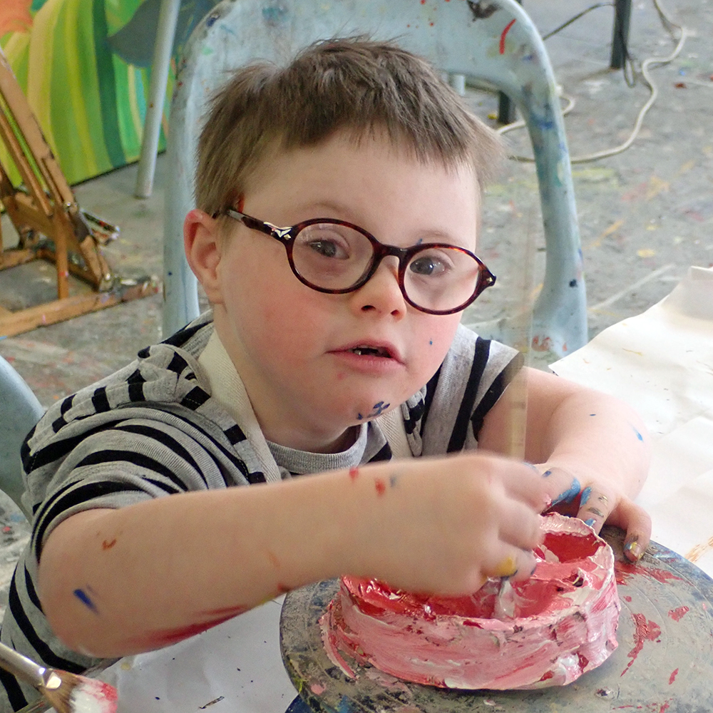 Young boy using red and white paint to paint a clay mould