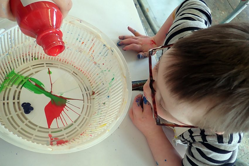 a birdseye view of a you boy with a hand pouring red paint into a colander to do a splatter paint picture.