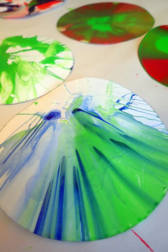 close up of circular white card with different coloured splatter paint designs