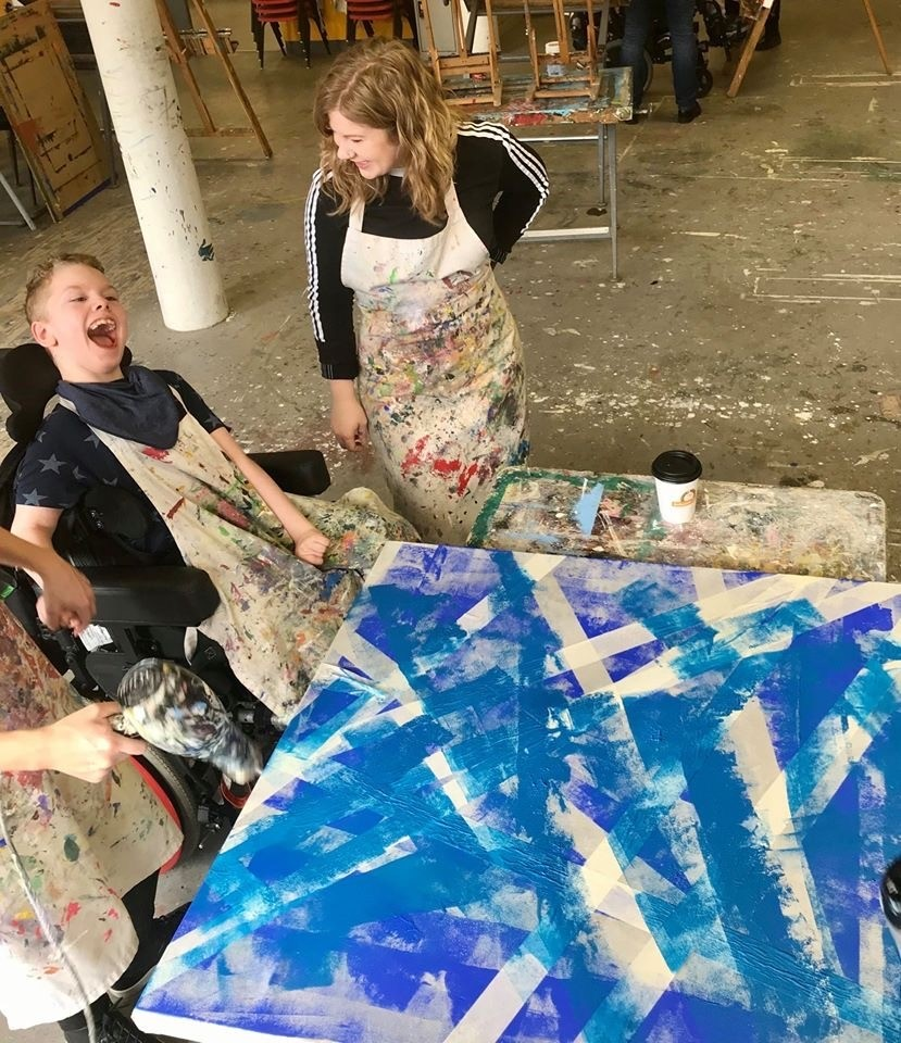 Vivian, a volunteer stading with one of the young participants showing his artwork